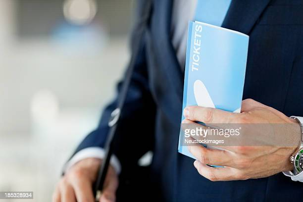 Businessman Holding Airplane Ticket At Airport