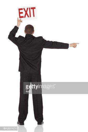 出口を降りて、サインボードを掲げているビジネスマン