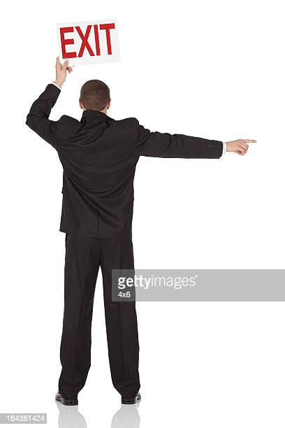 Businessman holding an exit signboard