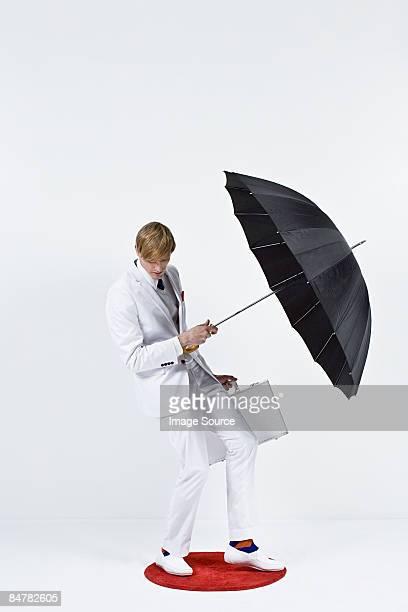 A businessman holding an umbrella