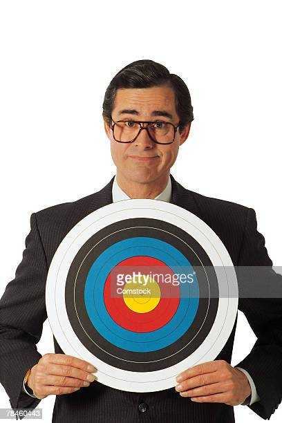 Businessman holding archery target
