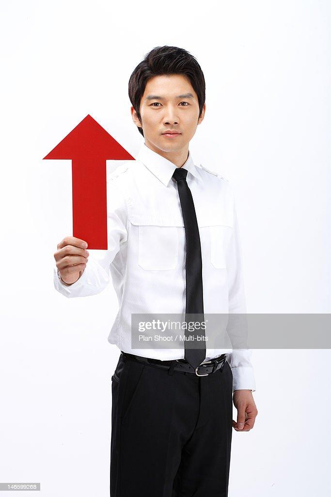 Businessman holding arrow sign : Stock Photo