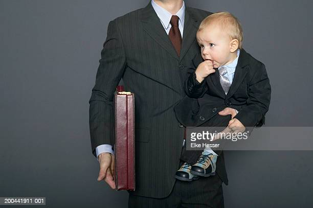 Businessman holding baby son (18-24 months) and briefcase under arm