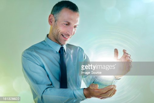 Businessman holding ball of light