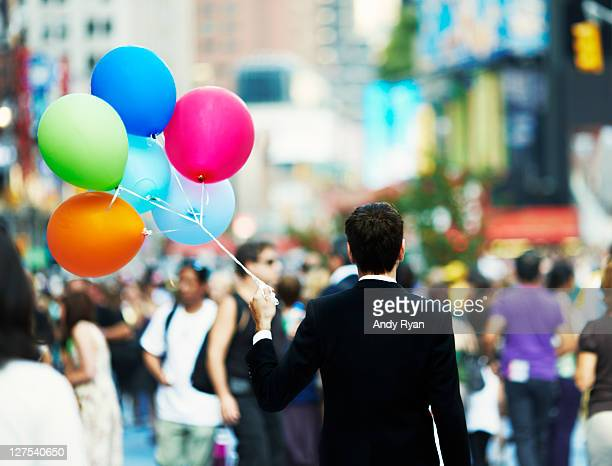 Businessman holding balloons in crowd.