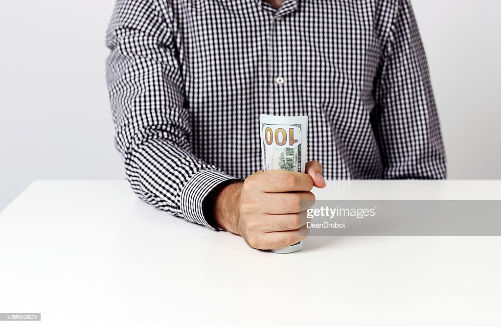 businessman holding banknotes at desk : Stock Photo