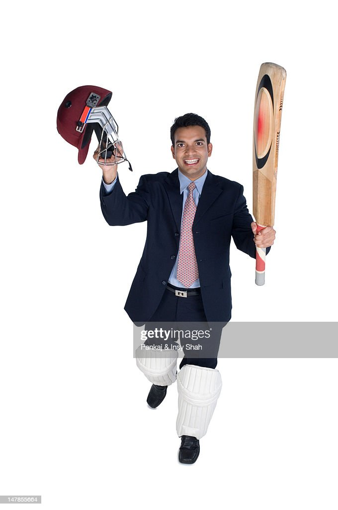 Businessman holding bat and sports helmet, smiling, portrait : Stock Photo