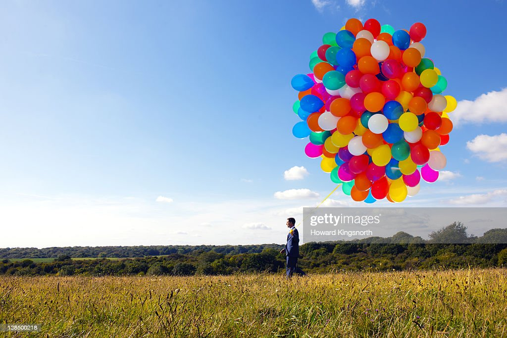businessman holding big bunch of balloons : Stock Photo