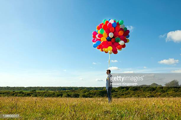 businessman holding big bunch of balloons