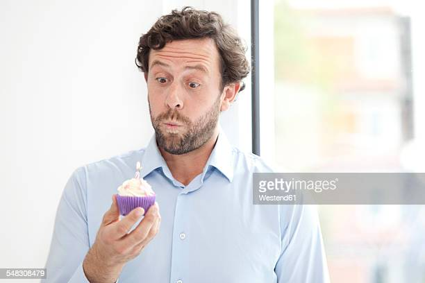 Businessman holding birthday cupcake