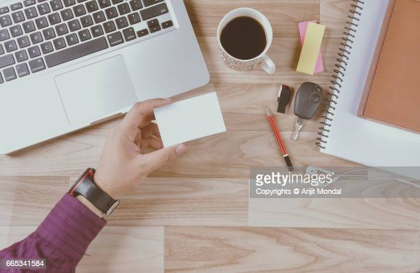 Businessman holding blank business card with laptop at office desk retro style top view