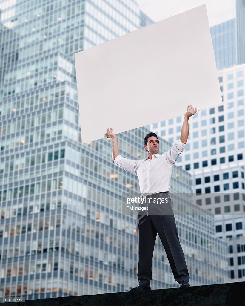Businessman holding blank sign : Stock Photo