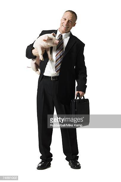 Businessman holding briefcase and piglet