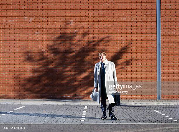 Businessman holding briefcase in empty car park