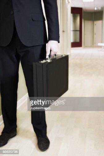 Businessman holding briefcase : Stock Photo