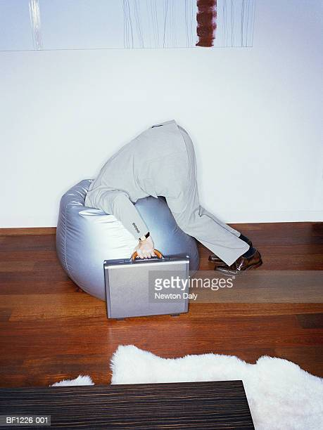 Businessman holding briefcase with head in bean bag