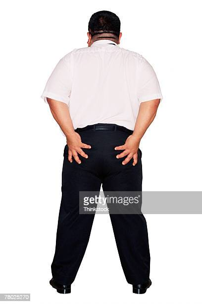 Businessman holding buttocks in rude gesture