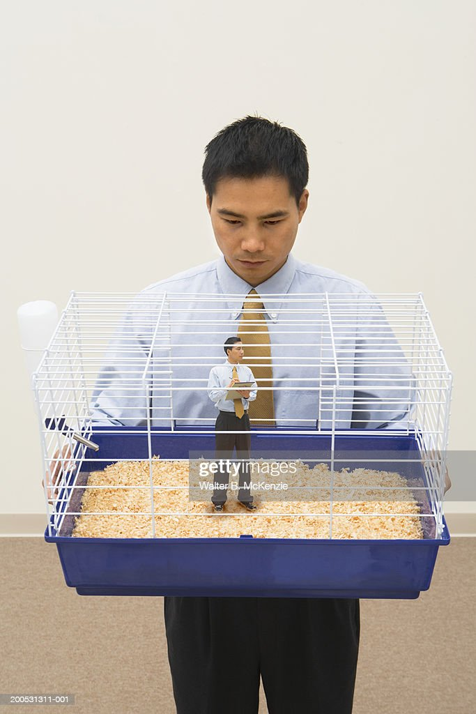 Businessman holding cage with miniature man taking notes : Stock Photo