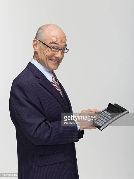 Businessman holding calculator, side view, portrait