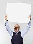 Businessman holding white cardboard, portrait, close-up