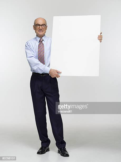 Businessman holding white cardboard, portrait