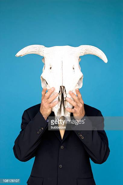 Businessman Holding Cattle Animal Skull Against Face