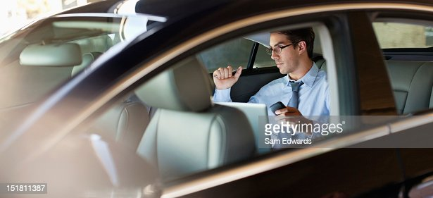 Businessman holding cell phone and using laptop in back seat of car : Stock Photo