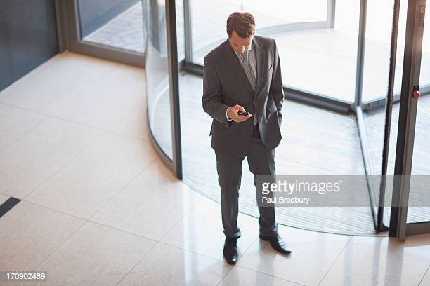 Businessman holding cell phone near revolving doors