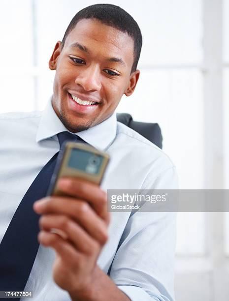 Homme d'affaires en tenant le téléphone portable et souriant