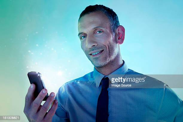 Businessman holding cellphone with lights