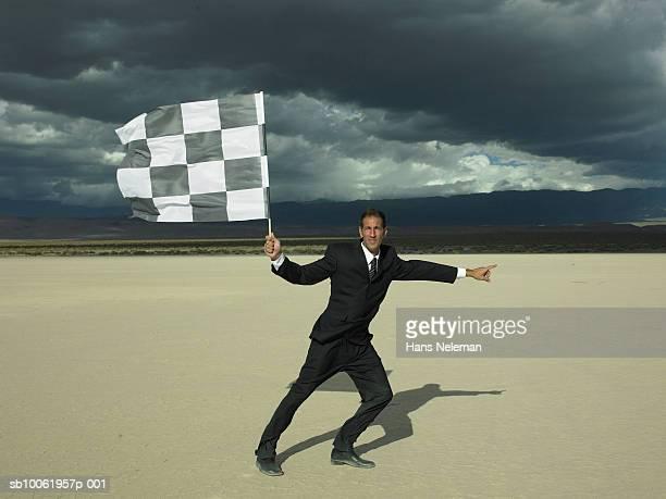 Businessman holding checkered flag in desert
