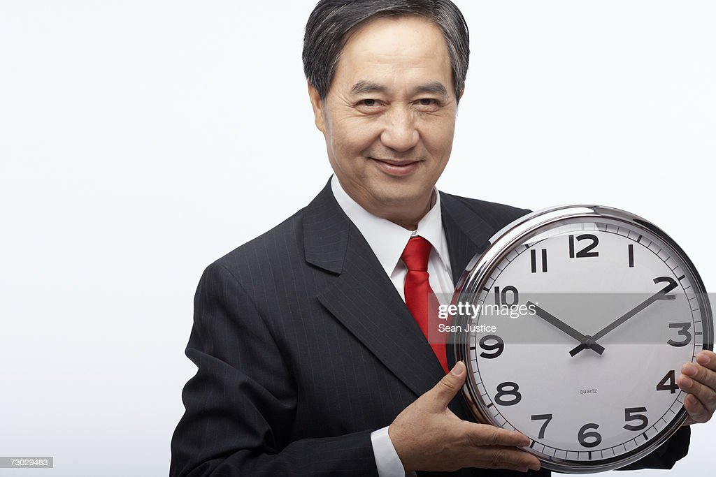 Businessman holding clock, portrait : Stock Photo