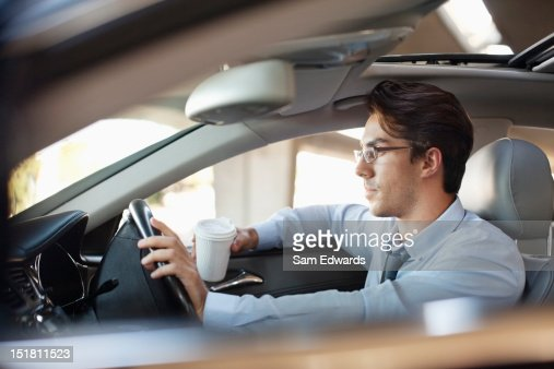 Businessman holding coffee cup and driving car : Stockfoto