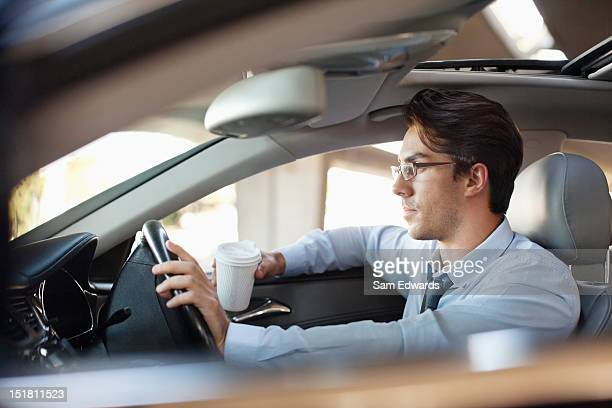 Businessman holding coffee cup and driving car