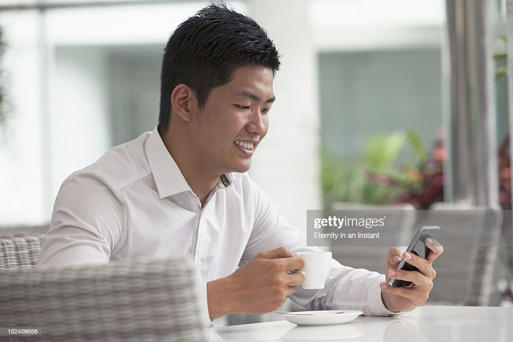 Businessman holding coffee cup and smartphone : Stock Photo