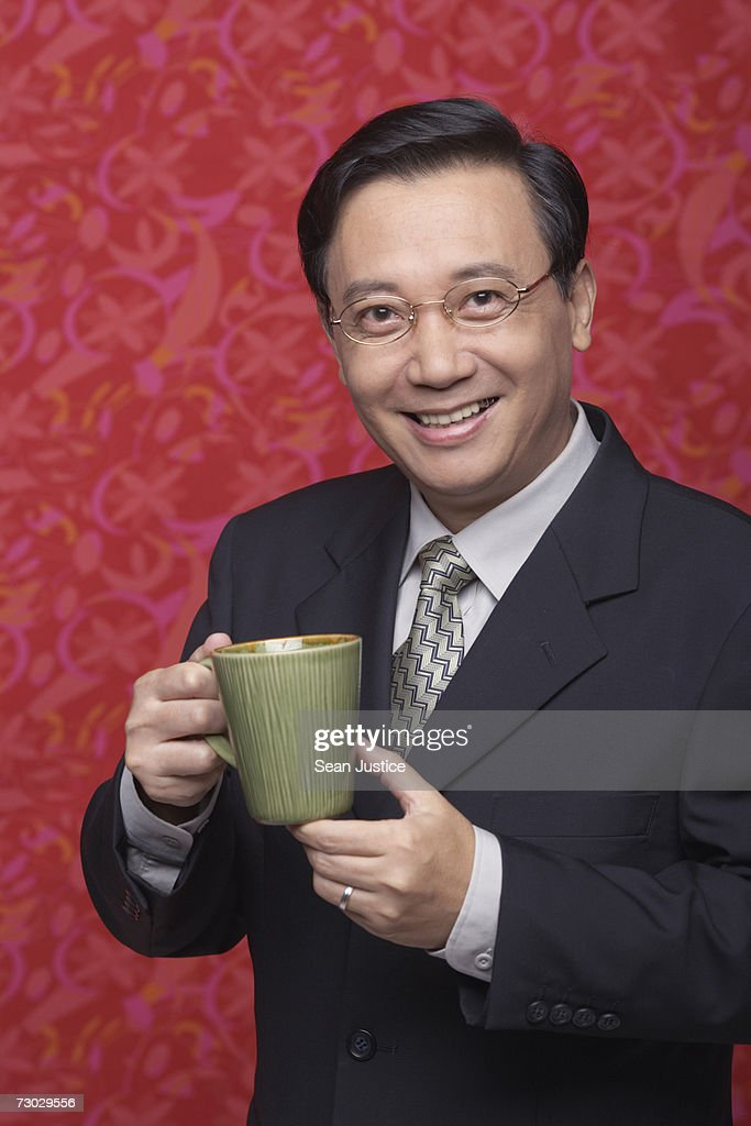 Businessman holding coffee cup, portrait : Stock Photo