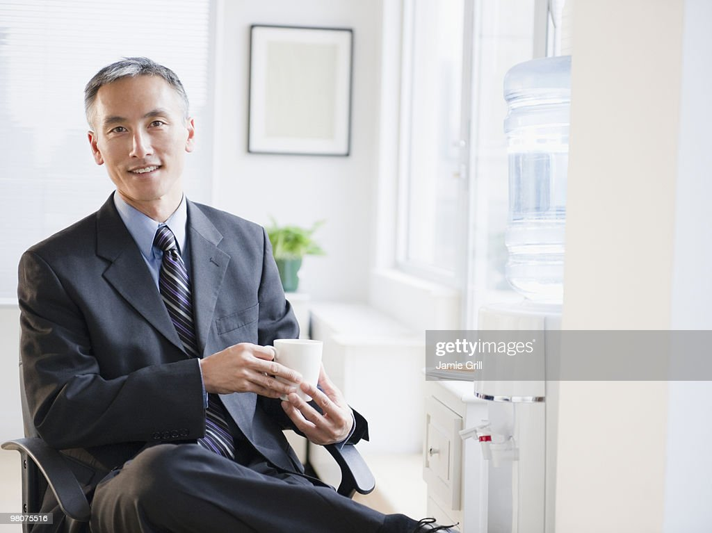 Businessman holding coffee, smiling : Stock Photo