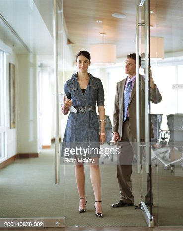 Businessman holding conference room door for businesswoman