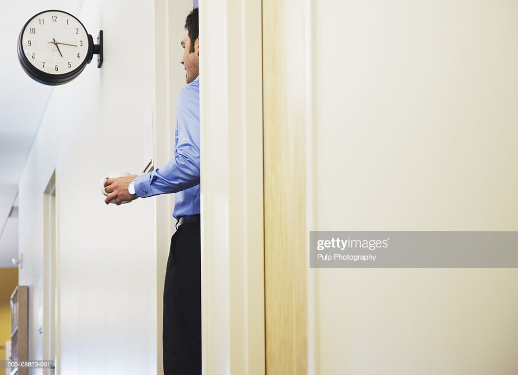 Businessman holding cup of coffee, standing in office doorway : Stock Photo