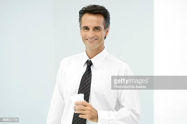 Businessman holding cup, smiling, portrait