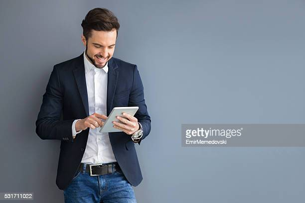 Businessman holding digital tablet in an office building hallway.