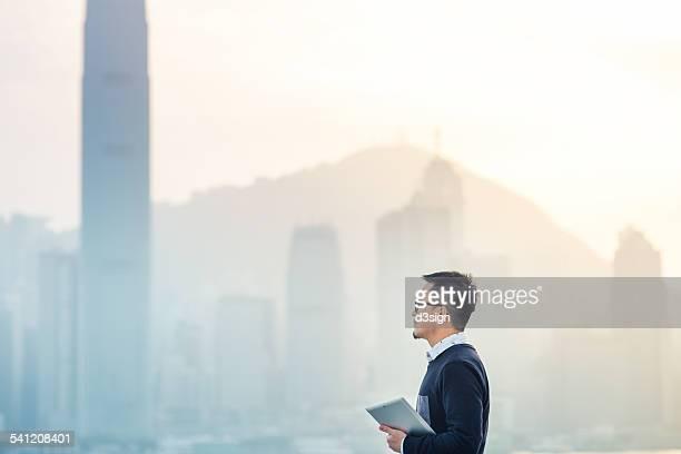 Businessman holding digital tablet in urban city