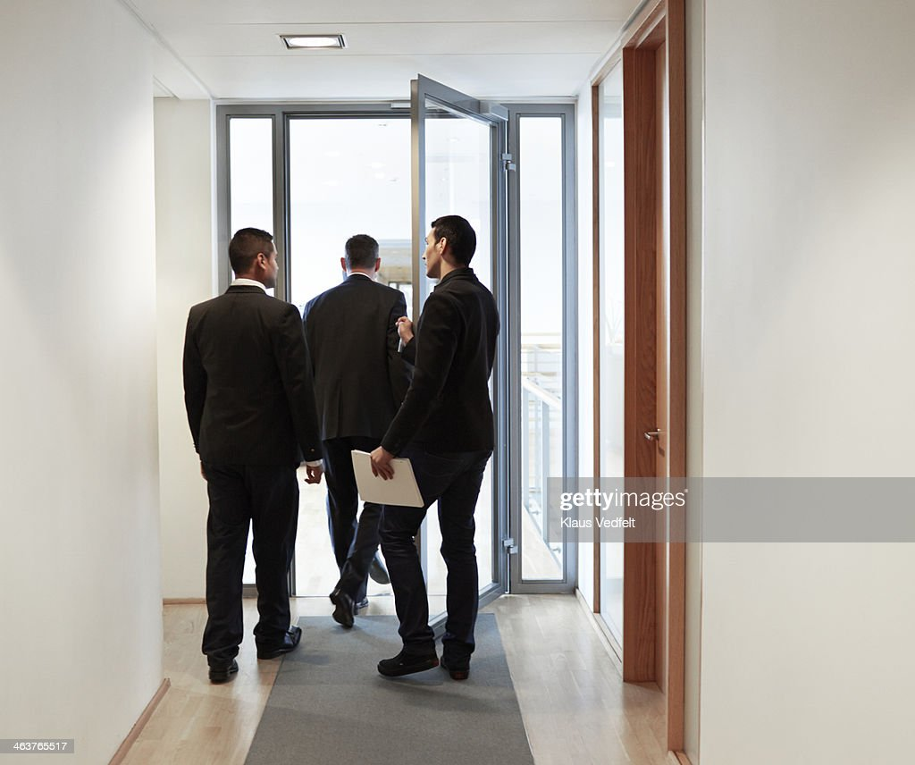 Businessman holding door for client : Stock Photo