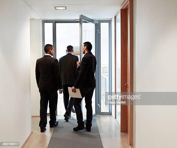 Businessman holding door for client