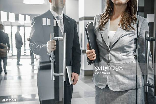 Businessman holding door open for female colleague