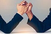 Businessman Holding Each Other Hands Over Desk, arm wrestling over