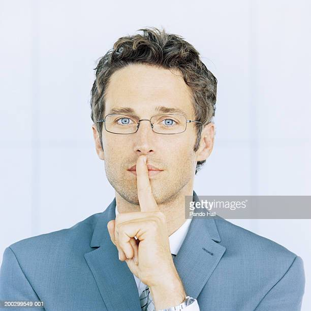 Businessman holding finger to mouth, portrait, close-up