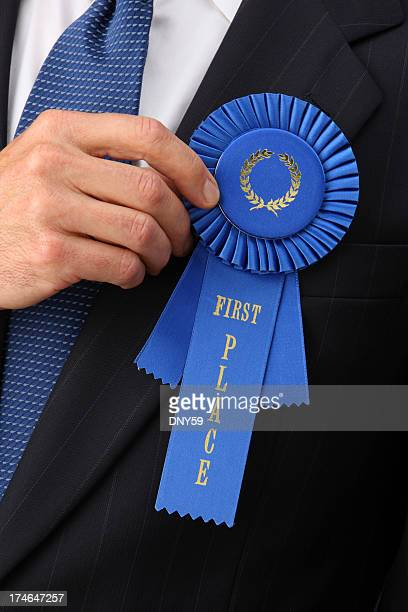 Businessman holding first place blue ribbon to his chest
