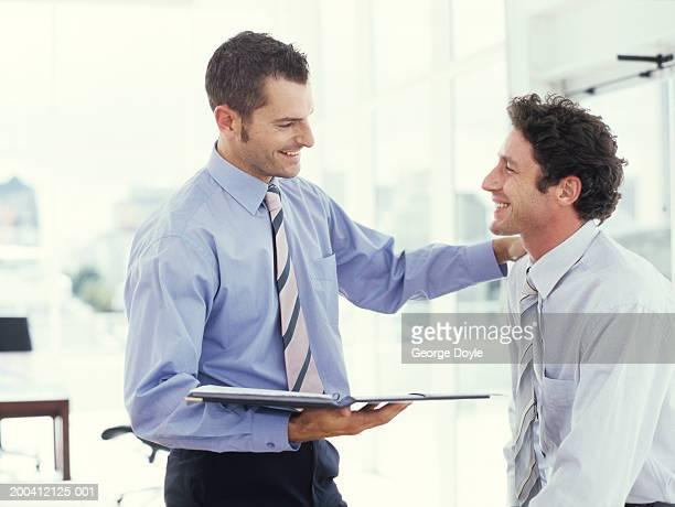 Businessman holding folder and putting hand on man's shoulder, smiling