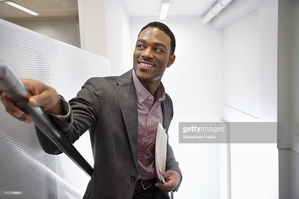 Businessman holding folder and standing on office stairs : Stock Photo